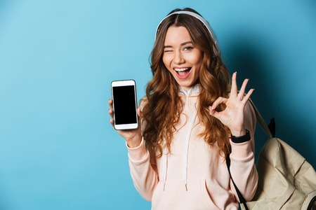 Portrait of a happy cheerful girl student with backpack listening to music with headphones while holding blank screen mobile phone and showing ok gesture isolated over blue background