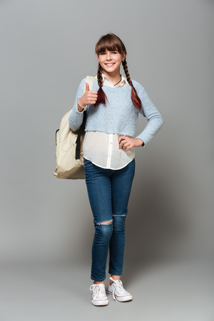 Full length portrait of a young schoolgirl with backpack standing and showing thumbs up gesture isolated over gray background