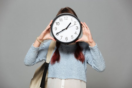 Image of girl standing isolated grey background covering face with clock in hands. Banco de Imagens