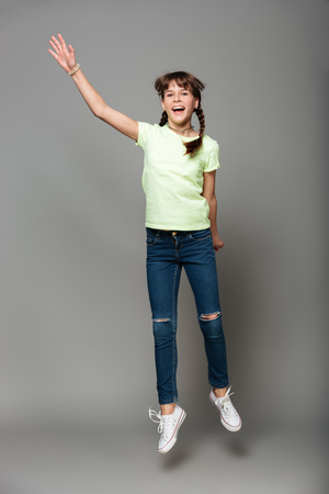 Image of cheerful girl jumping isolated grey background. Looking camera. Stock Photo