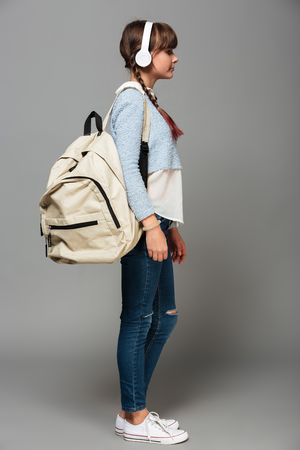 Side view photo of girl standing isolated grey background listening music with headphones. Looking aside holding backpack.