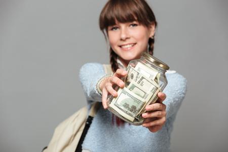 항아리 가득 돈을 격리 된 회색 배경 서 웃는 소녀의 그림. 배낭을 들고 카메라를 찾고 있습니다.