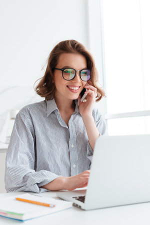 Close-up portrait of happy young woman in striped shirt talking on smartphone while using laptop computer at home Imagens