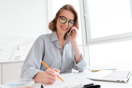 Beautiful smiling girl in glasses talking on mobile phone while working with documents at home 스톡 콘텐츠