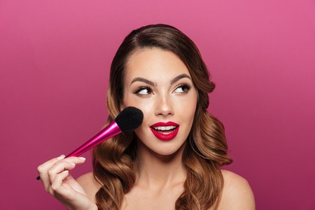 Pretty caucasian lady with make up brush looking aside and smiling isolated over pink