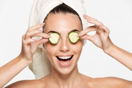 Close up beauty portrait of a healthy happy half naked woman with a towel wrapped around her face holding cucumber slices at her face and looking at camera isolated over white background