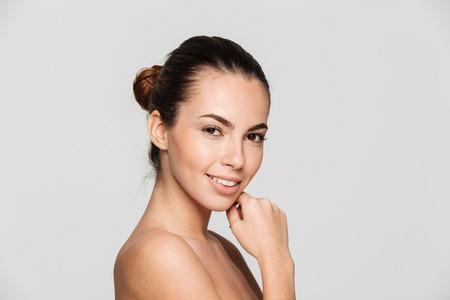 Schönheitsporträt einer lächelnden jungen halben Nackte mit der perfekten Haut, welche die Kamera lokalisiert über weißem Hintergrund aufwirft und betrachtet Standard-Bild