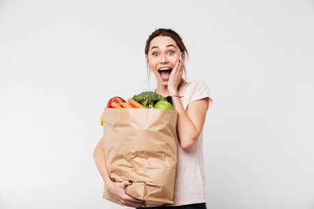 Portrait of a happy excited girl holding bag with groceries and screaming isolated over white background