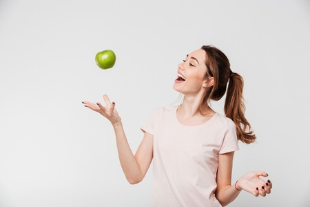 Portrait of a smiling happy girl throwing apple in the air isolated over white background Imagens