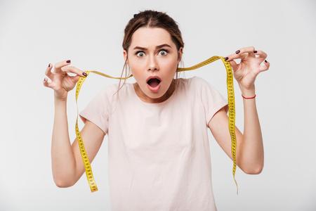 Portret van een geschokt jong meisje met open mondholding die band meten en camera bekijken die over witte achtergrond wordt geïsoleerd Stockfoto