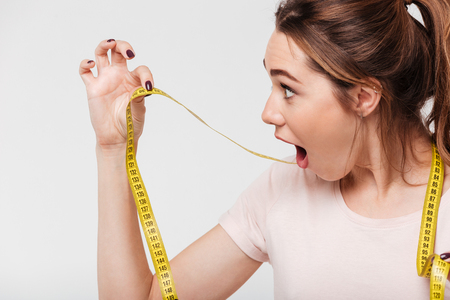 Close up portrait of a surprised young girl with open mouth looking at a measuring tape isolated over white background