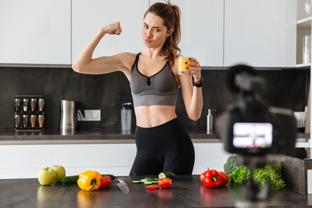 Cheerful healthy young girl recording her blog episode about healthy food diet while standing at the kitchen at home and flexing biceps Stock Photo