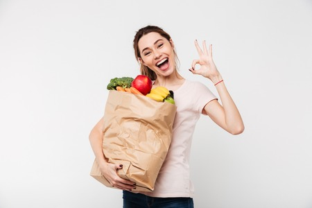 Close up portrait of a happy pretty girl holding bag with groceries and showing ok gesture isolated over white background Stockfoto