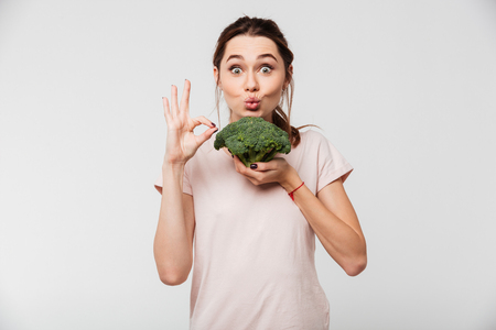 Portrait of a cheerful pretty girl holding broccoli and showing ok gesture isolated over white background 免版税图像