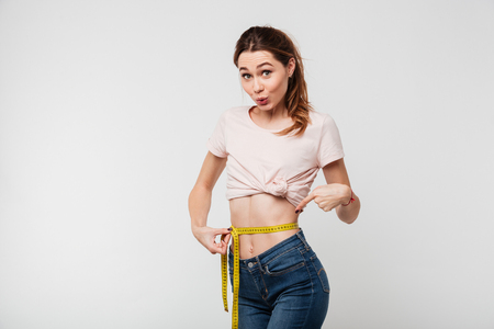 Portrait of a slim pretty woman holding measuring tape around her waist and pointing finger isolated over white background