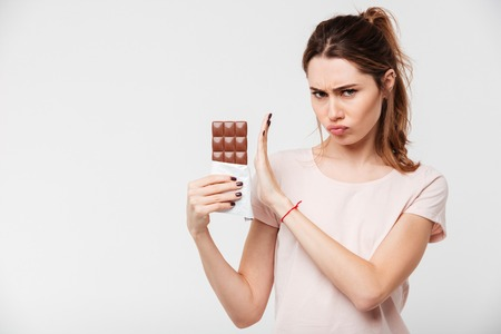 Portrait of a serious pretty girl refusing to eat chocolate bar with a hand gesture isolated over white background