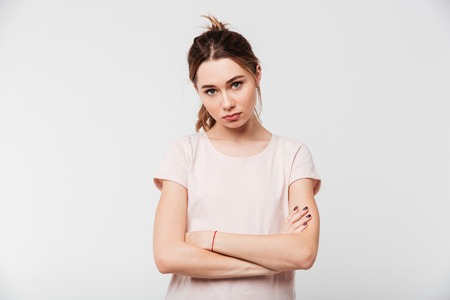 Portrait of an upset pretty girl standing with arms folded isolated over white background