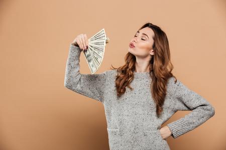 お金のファンと手を振って目を閉じた豪華なブルネイの女性の肖像画,ベージュの背景の上に隔離
