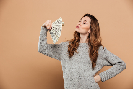 Portrait of gorgeous brunnete woman with closed eyes waving with fan of money, isolated over beige background