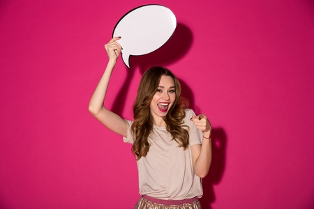 Photo of happy pretty young woman standing isolated over pink background. Looking camera holding speech bubble over head pointing to you.