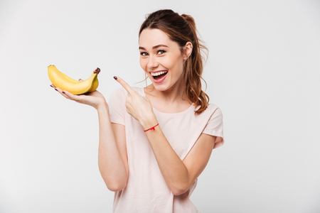 Portrait of a cheerful young girl holding bananas and pointing finger isolated over white background