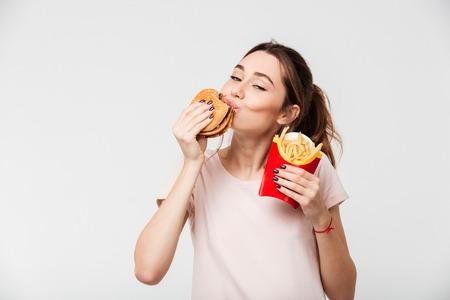 Sluit omhoog portret van een tevreden mooi meisje die frieten en een hamburger eten die over witte achtergrond wordt geïsoleerd