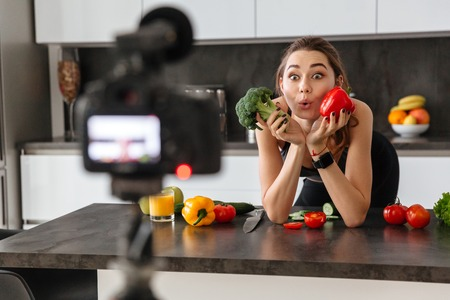 Cheerful healthy young girl recording her blog episode about healthy food diet while standing at the kitchen at home