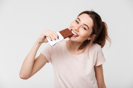 Portrait of a smiling pretty girl biting chocolate bar and looking at camera isolated over white background