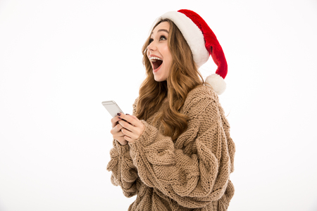 Cheerful young woman dressed in warm sweater wearing christmas hat standing isolated over white wall background. Looking aside chatting by phone. Stock Photo