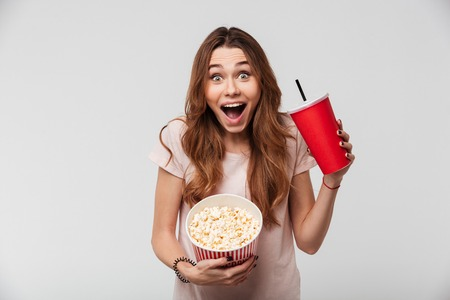 Portrait of a cheerful pretty girl holding plastic cup and popcorn isolated over white background 版權商用圖片