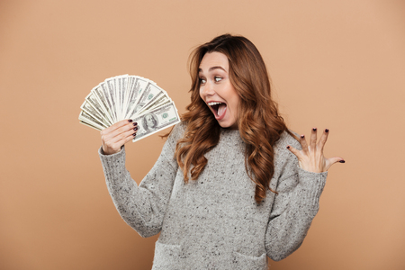 Happy exited attractive girl holding bunch of money, looking aside, isolated over beige background
