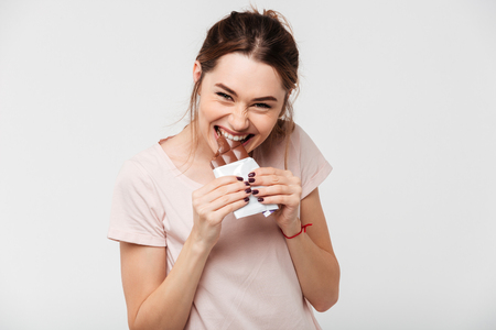 Portrait of a hungry pretty girl biting chocolate bar and looking at camera isolated over white background Stock Photo