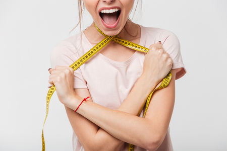 Cropped image of a screaming girl strangling herself with a measuring tape isolated over white background