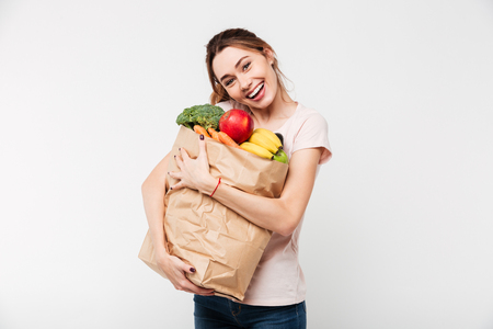 Close up portrait of a happy pretty girl holding bag with groceries isolated over white background Stock fotó