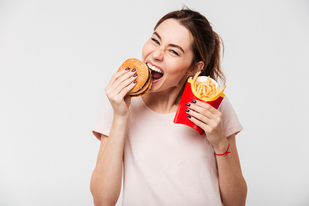 Close up portrait of a happy pretty girl eating french fries and a burger isolated over white background