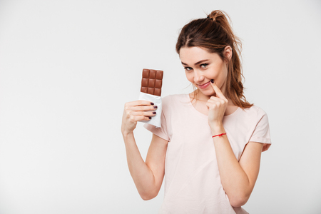 Portrait of a lovely pretty girl holding chocolate bar and looking at camera isolated over white background