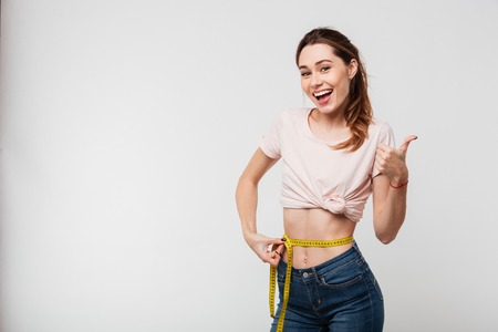 Portrait of a slim satisfied woman holding measuring tape around her waist and showing thumbs up isolated over white background
