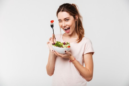 Portrait of a happy playful girl eating fresh salad from a bowl and winking isolated over white background