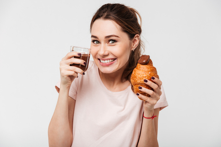 Portrait of a satisfied pretty girl eating croissant and chocolate pudding from a glass isolated over white background