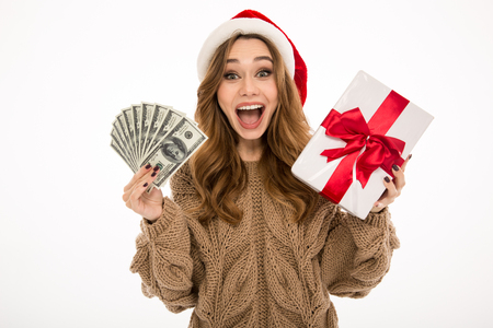 Excited shocked young woman dressed in warm sweater wearing christmas hat standing isolated over white wall background. Looking camera holding money and surprise gift box.