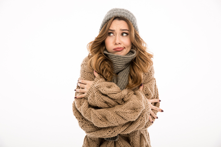 Displeased freezing young woman dressed in warm sweater and scarf standing isolated over white wall background. Looking aside. 스톡 콘텐츠