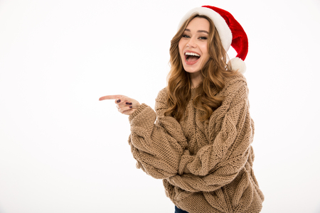 Smiling young woman dressed in warm sweater wearing christmas hat standing isolated over white wall background. Looking camera pointing to copyspace.