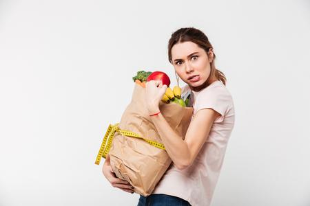 흰색 배경 위에 절연 식료품 가방을 들고 욕심이 여자의 초상화 스톡 콘텐츠