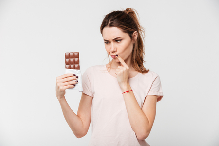 Portrait of a thoughtful pretty girl holding chocolate bar isolated over white background