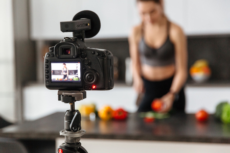 Close up of a camera recording healthy food tutorial with a girl indoors Stock Photo