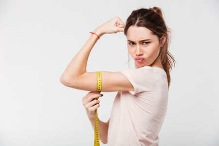 Portrait of a confident fit girl flexing biceps with a measuring tape around her arm isolated over white background 스톡 콘텐츠