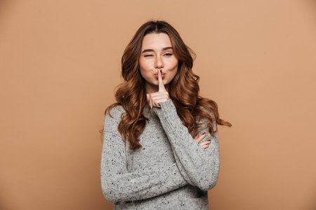 Close-up portrait of funny brunette girl blinks one eye while showing silence gesture, isolated on beige background 스톡 콘텐츠