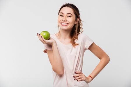 Portrait of a smiling pretty girl holding an apple and looking at camera isolated over white background Stock Photo