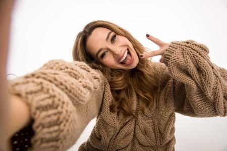 La imagen de la mujer linda feliz vestida en el suéter caliente que se sienta en el piso aislado sobre el fondo blanco de la pared hace el selfie por la cámara que muestra gesto de la paz. Foto de archivo - 91706858