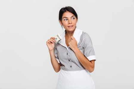 Close-up photo of female housekeeper in uniform hiding her tips and looking aside, isolated on white background Stock Photo
